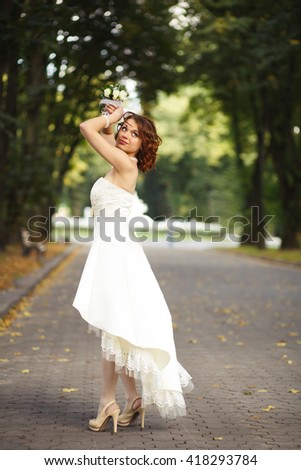 Watch my train - bride poses on the path in a park - stock photo