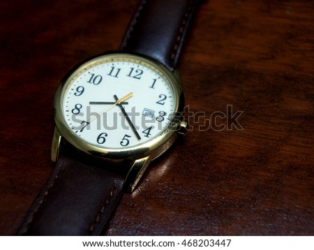 Watch on wooden table.