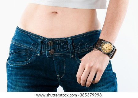 Watch with a leather strap on a female hand near her hips in jeans .