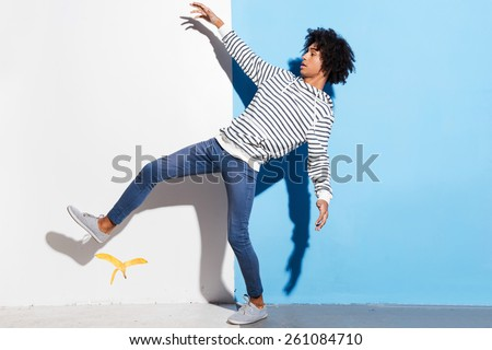 Watch your step! Handsome young African man slipping against colorful background  - stock photo