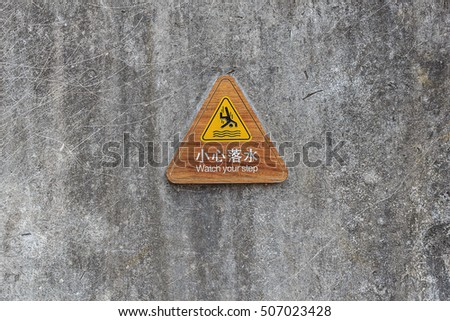 Watch your Step Sign, Wooden sign in Chinese and English to prevent from falling to water on old concrete wall