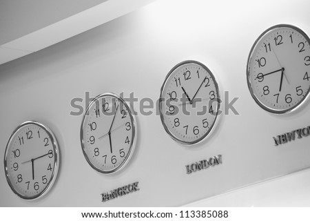Watches dial plates diferent time zones on the wall - stock photo