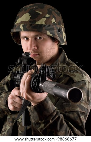 Watchful soldier aiming  m16 in studio. Isolated