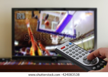 Watching a basketball match in the television, with a tv remote control in the hand - stock photo