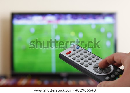 Watching a football match in the television, with a tv remote control in the hand