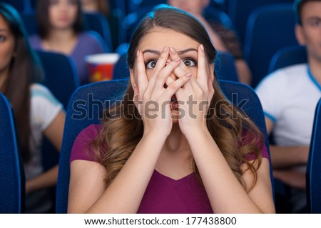 Watching a scary movie. Shocked young woman covering face with hands and watching movie while sitting at the cinema  - stock photo