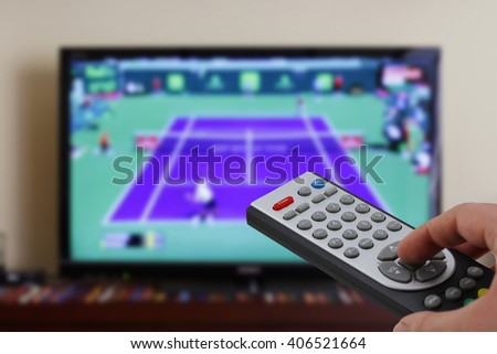 Watching a tennis match in the television, with a tv remote control in the hand