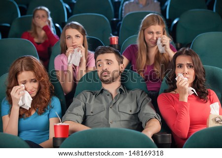 Watching drama. Handsome young men looking bored while women crying during the movie session in the cinema
