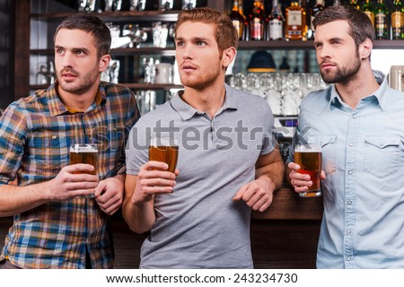 Watching football at the bar. Three handsome young men in casual wear holding glasses with beer and looking away while standing at the bar counter - stock photo