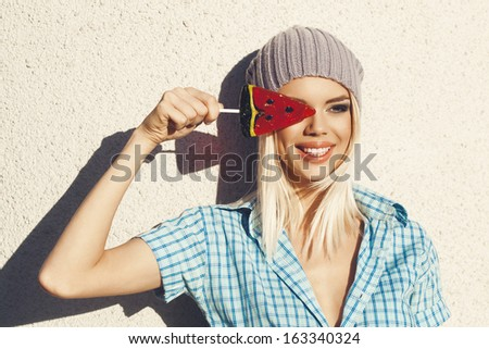 Watching on the sun through the watermelon lollipop. Outdoors, lifestyle. - stock photo