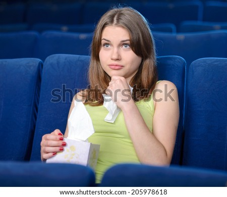 Watching romantic movie. Thoughtful young women watching movie at the cinema - stock photo