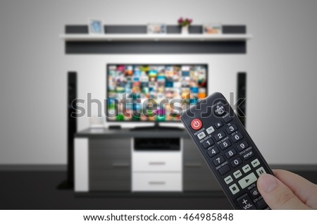 Watching television in modern TV room. Hand holding remote control