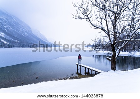Watching the coming of a snow storm over frozen lake Bohinj in Slovenian Alps - stock photo