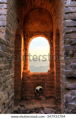 Watching the sunrise from a guard tower in the un-restored Great Wall in China.