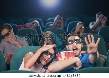 Watching three-dimensional movie. Terrified people in three-dimensional glasses watching movie at the cinema and gesturing - stock photo