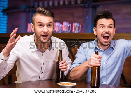 Watching TV in bar. Two happy young men are drinking beer and gesturing while sitting in bar. - stock photo
