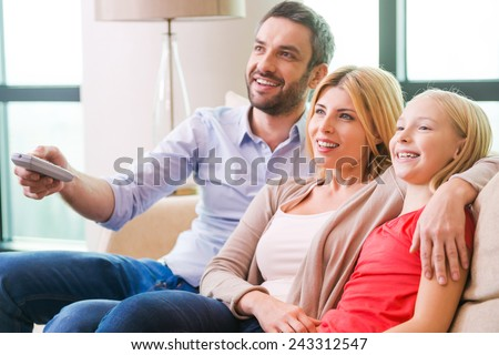Watching TV together. Happy family of three bonding to each other and smiling while sitting on the couch and watching TV together