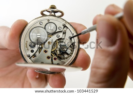 Watchmaker holding antique pocket watch show the clockwork mechanism and repair with screwdriver.