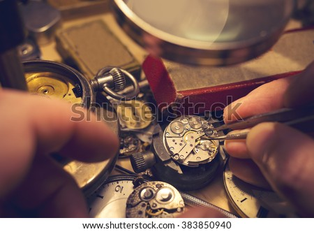 Watchmakers Craftmanship. A watch maker repairing a vintage automatic watch. - stock photo