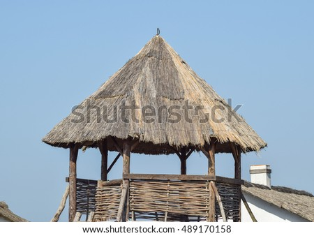 Watchtower with a thatched roof. Wooden observation tower.
