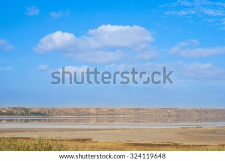water and a steep bank against the sky - stock photo
