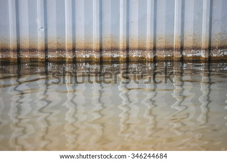 water at the floor with Rusted galvanized iron plate after flood in Bangkok , Thailand stain pattern  - stock photo