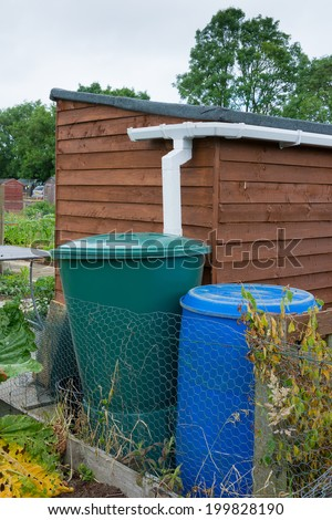 Water barrels attached to garden shed - stock photo