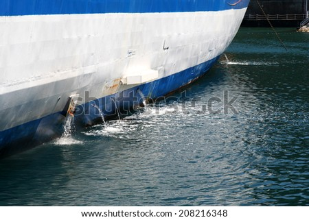 Water being pumped from the bilges of a boat. - stock photo