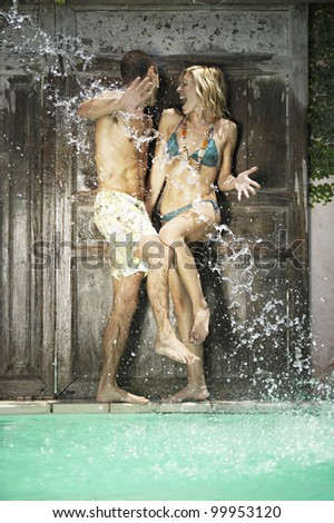 Water being splashed onto a young couple in swimwear by a swimming pool. - stock photo