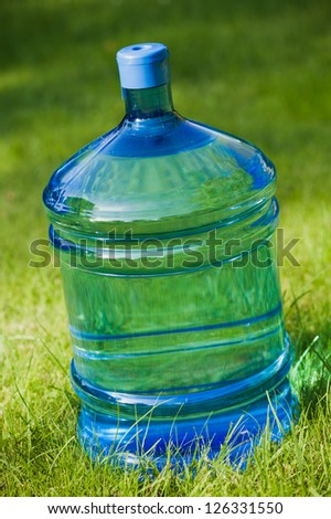 water big bottle on green lawn background - stock photo