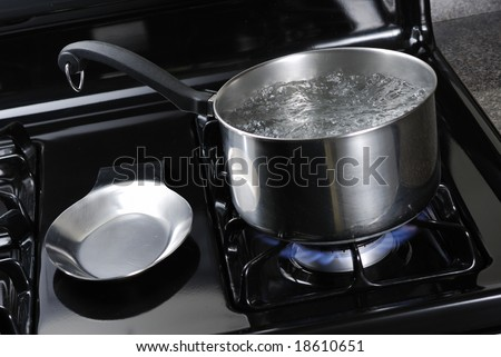 Water boiling in a stainless steal pot on a black stove. - stock photo