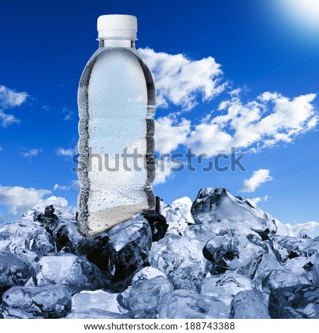 Water bottle on ice cubes with blue sky background - stock photo