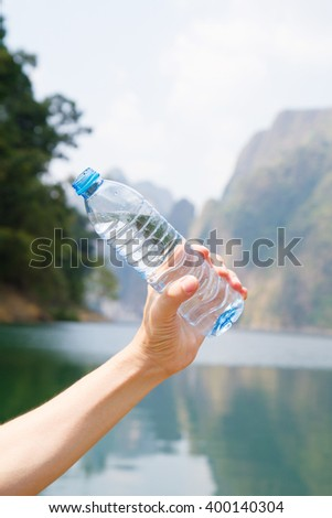 Water Bottle on right hand and fresh background