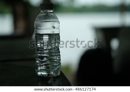 Water bottle on wooden table with bokeh background in park