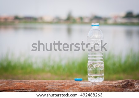 Water bottle put on wood in garden,soft focus.