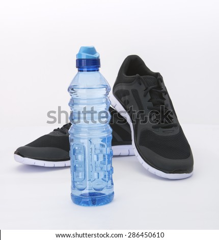 Water bottle to hydrate runner in black shoes