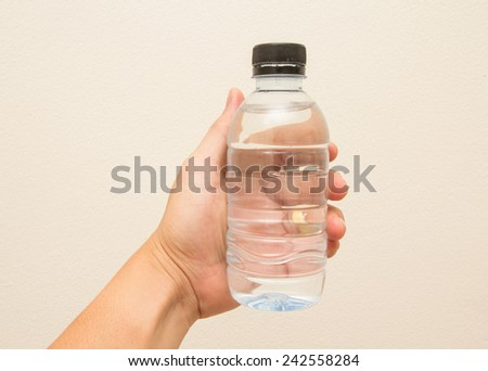 Water bottle with Hand on Cream color Background - stock photo