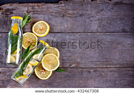 Water bottle with lemon and mint on a wooden table. Infused water with lemon, cucumber and mint on wooden background. Mineral water.summer drink. - stock photo