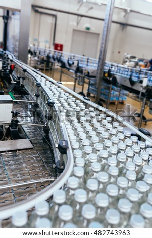 Water bottling line for processing and bottling pure mineral water into small white glass bottles. Selective focus.