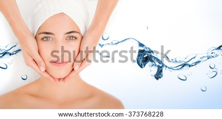 Water bubbling on white surface against attractive woman receiving facial massage at spa center - stock photo
