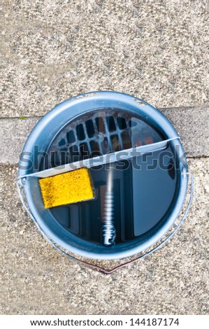 Water bucket with a windscreen wiper and a sponge - stock photo
