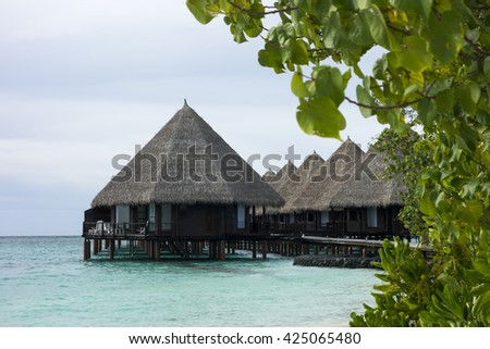 water bungalow against the blue ocean and tropical vegetation