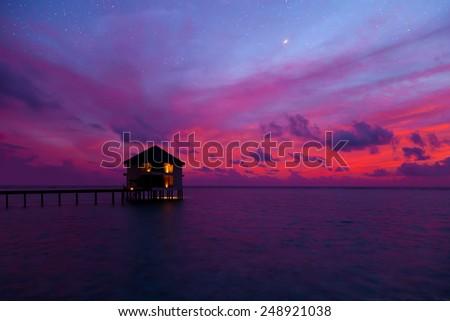 Water bungalow and sunset on Maldives island - stock photo