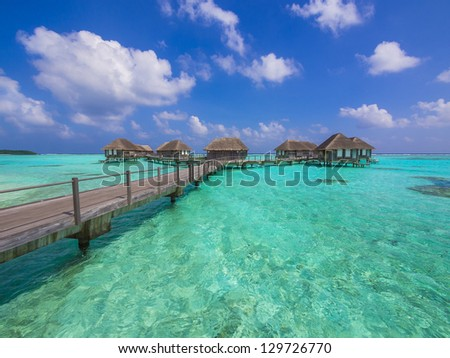 Water bungalows at a tropical island - travel background - stock photo