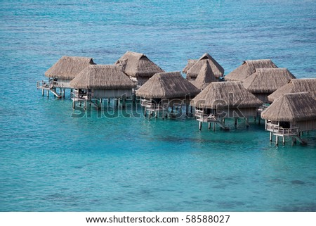 Water bungalows in the lagoon of Moorea, French Polynesia. - stock photo