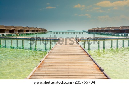 Water bungalows of an island resort extend into the lagoon in Maldives - stock photo