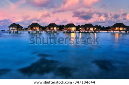 Water bungalows with beautiful twilight sky and sea in Maldives. Long Exposure. - stock photo