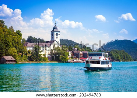 Water bus crossing Wolfgangsee and arriving in St. Wolfgang, Austria - stock photo