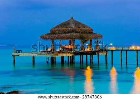 Water cafe at evening, lights, ocean and sky - stock photo