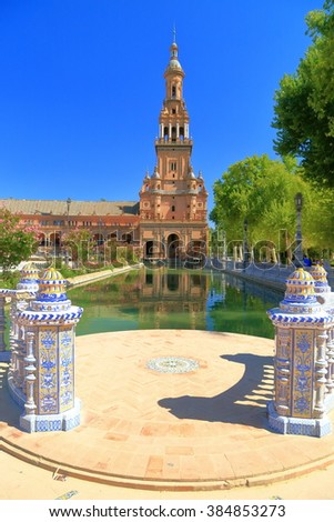 Water canal in front of a tower of the Renaissance building in Plaza de Espana (Spain Square) in Seville, Andalusia, Spain
